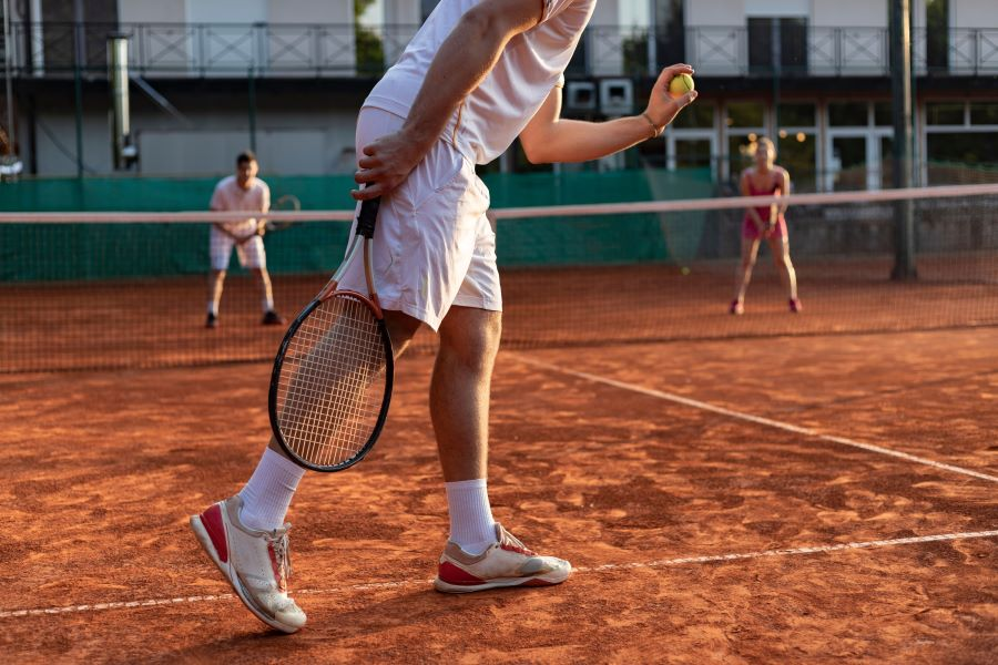 Tennis player about to serve on clay court