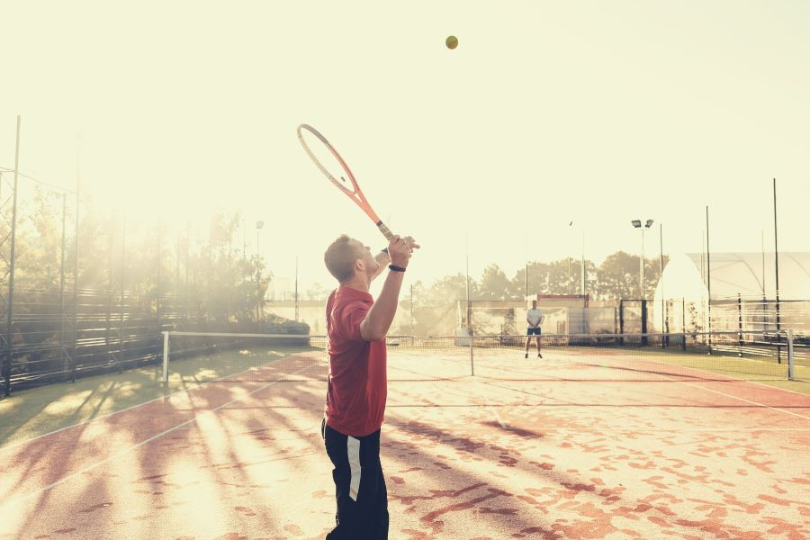One player serving on damp and cold outdoor tennis court