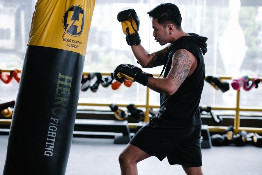 Boxer hitting punch-bag in gym