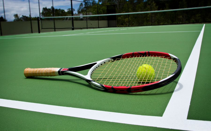 Tennis racket with ball on a court