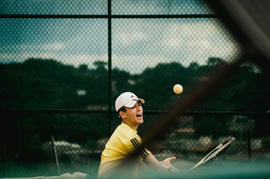 Man grimacing while playing tennis