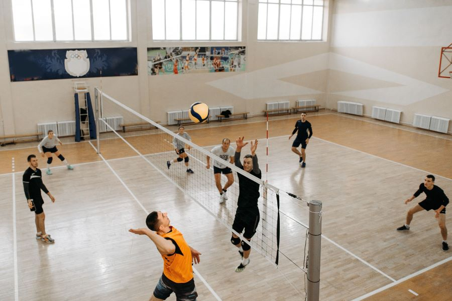 Two teams playing volleyball in a gymnasium