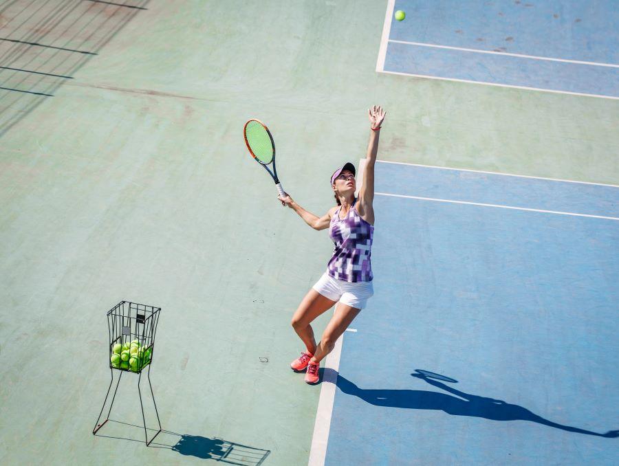 Female tennis player serving on a hardcourt