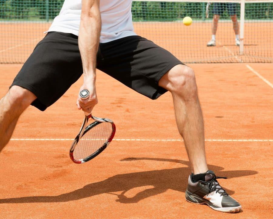 Tennis player trying a trick-shot, hitting a ball between his legs